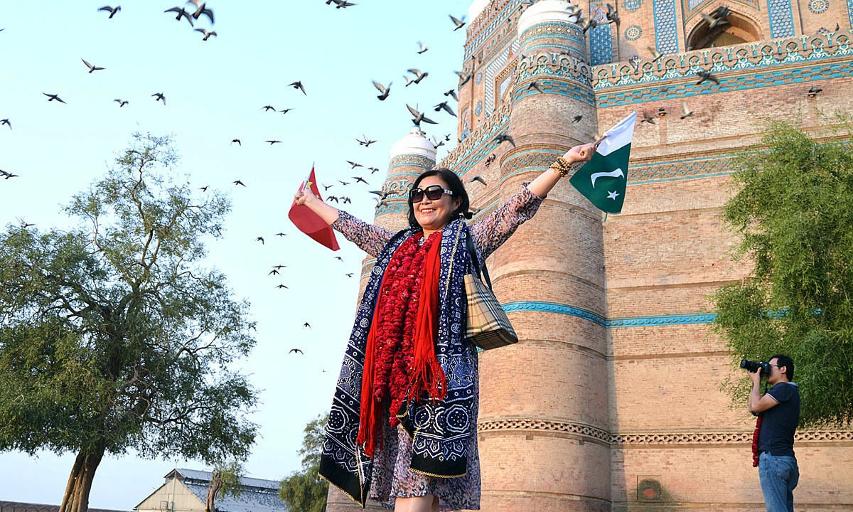 APP63-19 MULTAN: October 19 - Participant of Pak-China Friendship Car Rally express happiness while carrying flags of China and Pakistan during visit of Historical Fort Shah Rukne Alam. APP photo by GM Kashif